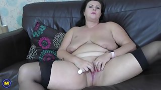 Fat brunette with saggy tits is wearing black stockings while masturbating like crazy, on the sofa